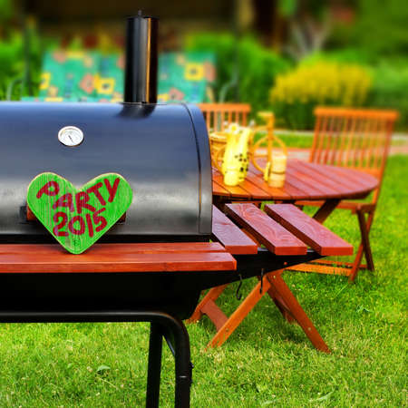 BBQ Party Sign on Wooden Heart at Barbecue Appliance on the Backyard at Summertime. Outdoors Furniture on the background. photo