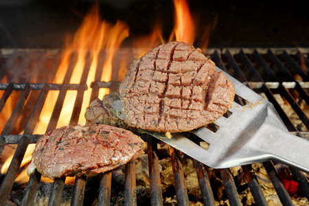 Beefsteak on the Spatula. Flaming BBQ Grill in Background photo