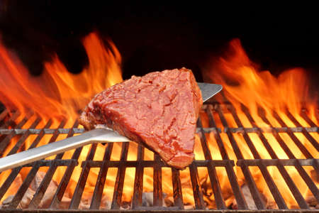barbequing: Raw Beefsteak on the Blade Over a Hot BBQ Grill. Flames of Fire on the Black Background. Stock Photo