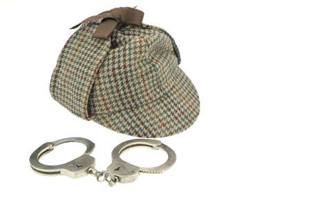Deerstalker or detective Hat and Real Steel Handcuffs  Isolated on White Background photo