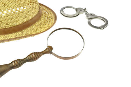 Retro Straw Hat, Magnifying Glass and Handcuffs  Isolated on White Background photo