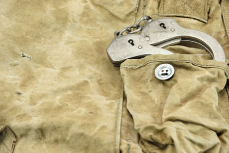 confiscation: Handcuffs in The Camouflage Army Pants Pocket or Haversack or Bag or Fabric. Backgrond  and Texture.
