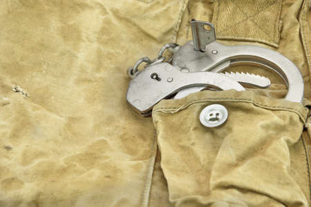 haversack: Handcuffs in The Camouflage Army Pants Pocket or Haversack or Bag or Fabric. Backgrond  and Texture.