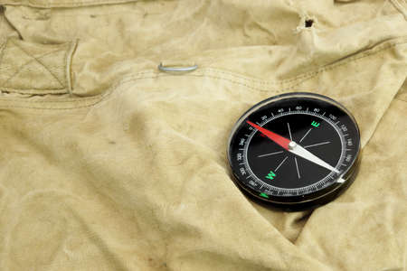duffel: Modern Magnetic Compass,  Old Camouflage  Handbag or Backpack on the Background Stock Photo