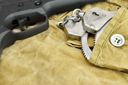 Black Handgun and Handcuffs On The Weathered Backpack photo