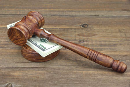 auctioneer: Judges or Auctioneer Gavel, Soundboard and Money Wad on Grunge Wood Table Stock Photo