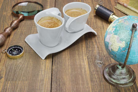 Earth Globe, Vintage Spyglass, Magnifying Glass, Compass, Two Notebooks, Smoking Pipe, and Two Espresso Coffee Cups On The Grunge Wooden Table photo