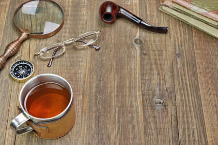 Traveler Items on Wooden Table. Tea Mug, Vintage Magnifying Glass, Compass, Two Retro Notebooks, Smoking Pipe, Glasses photo