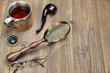 travel mug: Adventures Or Travel Or Expedition Items On Wooden Table. Tea Mug, Vintage Magnifying Glass, Compass, Smoking Pipe, Glasses