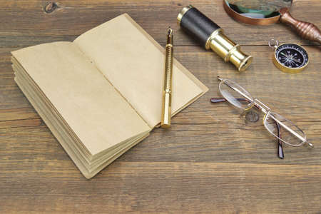 Open Vintage Notebook With Blank Pages, Gold Fountain Pen, Glasses, Retro Magnifier, Compass and Spyglass On Grunge Woodeen Table Background photo