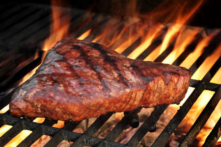Marinated Beef Steak On The Hot BBQ Charcoal Grill. Flame Of Fire In The Background. Stock Photo
