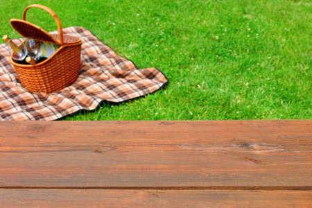 空の木製ピクニック テーブル トップのクローズ アップ。ピクニック バスケットやバック グラウンドで夏の芝生の毛布。