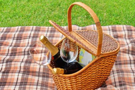 glas sekt: Picknick-Korb mit Teller, Essen, Wein Flaschen und zwei Weingl�ser auf der Decke Close-up. Sp?ing Lawn Auf Dem Hintergrund. Picknick im Freien oder Partei oder Szene.