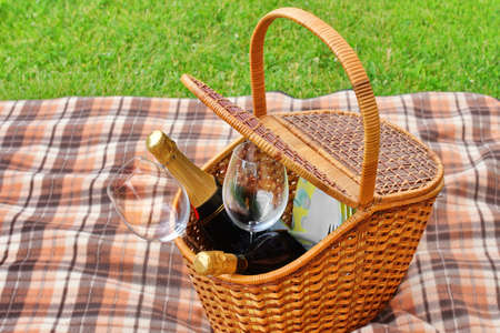 ing: Picnic Basket With Plates, Food, Wine Bottles And Two Wineglasses  On The Blanket Close-up. Spкing Lawn On The Background. Outdoor Picnic or Party or Scene. Stock Photo