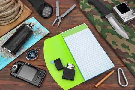 hip flask: Gear laid Out For A Backpacking Trip On A Rustic Wooden Grunge Floor Or Table. Items Include, Rope, Bag Or Backpack, Camouflage Wear or Raincoat or Vest or Pants, Hip Flask, Notebook or Open Book, Compass, Multifunction  Tools, Hunting Knife,  Searchlight Stock Photo