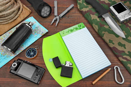 multifunction: Gear laid Out For A Backpacking Trip On A Rustic Wooden Grunge Floor Or Table. Items Include, Rope, Bag Or Backpack, Camouflage Wear or Raincoat or Vest or Pants, Hip Flask, Notebook or Open Book, Compass, Multifunction  Tools, Hunting Knife,  Searchlight Stock Photo