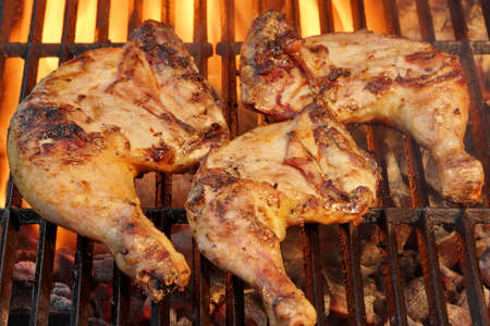 Marinated Chicken Legs Fried On The Hot Flaming BBQ Grill. Charcoal Flames On the Background.