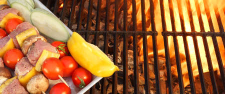 kebob: Meat And Vegetables Not Cooked Shish Kabobs On The Flaming Grill Close-up. Fire Of Flames In The Background. Stock Photo