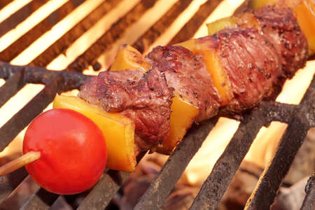 kabob: Weekend BBQ Meat Beef  Kebab Or Kabob On The Hot Flaming Grill. Flames of Fire on The Background. Summer Party or Picnic Food.