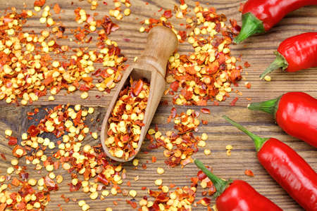milled: Hot Chili Peppers, Milled  Peppers Flakes and Corns In The Wood Spoon On Rustic Wooden Table Background.  Ingredients for Soup, Salad, Paste Stock Photo