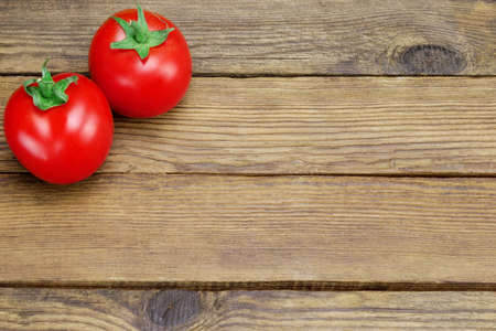 shinning leaves: Two Ripe Shinny Fresh Tomatoes On Rough Rustic Wood Tabletop Stock Photo
