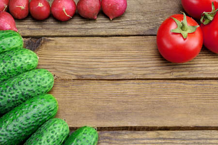 shinning leaves: Fresh Vegetables On The Kitchen Rustic Tabletop Background With Free Space. Tomatoes, Cucumbers, Radish