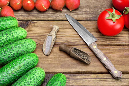 Fresh Vegetables And Knife On The Kitchen Rustic Rough Wooden Tabletop. Tomatoes, Cucumbers, Radish, Two Small Spoon With Pepper And Salt photo