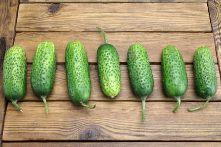 top seven: Fresh Seven Cucumbers In A Row On The Rough Rustic Wood Tabletop