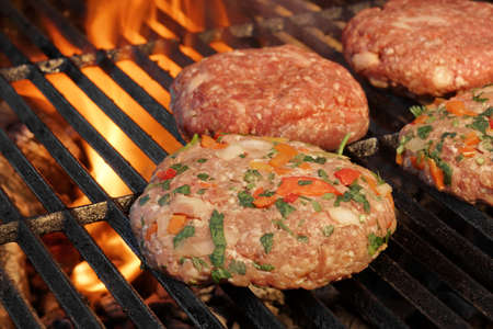 Tasty Burgers On The Barbecue Grill. Charcoal Flames On the Background. photo