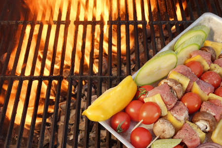 shishkabab: Meat And Vegetables Not Cooked Shish Kabobs On The Flaming Grill Close-up. Fire Of Flames In The Background. Stock Photo