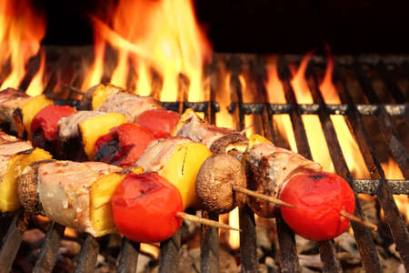 barbeque grill: Meat And Vegetable Kebabs On The Hot BBQ Grill Closeup. Flaming  Charcoal Grill In The Background. Snack For Outdoor Summer Barbeque Party. Stock Photo