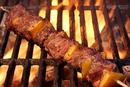 shishkabab: Beef Kebabs On The Hot BBQ Grill Closeup. Flaming  Charcoal Grill In The Background. Cookout Snack For Summer Spring Weekend  Barbeque or Picnic Party.