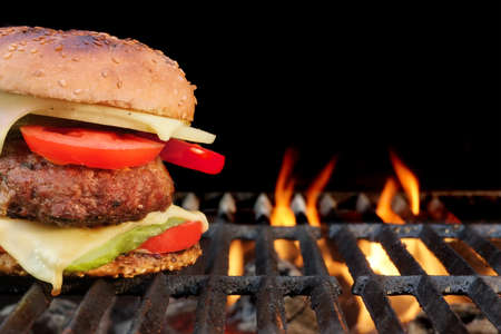 熱い炎のようなグリル自家製バーベキュー牛肉のハンバーガー。屋外の夏のパーティーやピクニックの良いおやつ