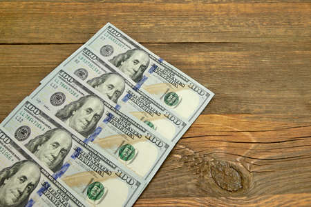 five dollar bill: Five New One Hudred Dollar Bill On The Rough Wood Background