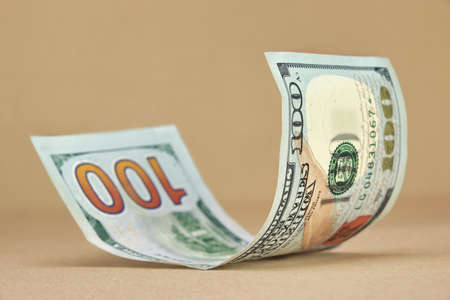 Rolled New American One Hundred Dollar Bill On The Beige Floor Background Stock Photo