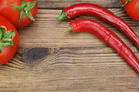 Two Fresh Red Hot Chili Peppers And Three Tomatoes On The Rustic Wood Kitchen Table. Background With Copy Space. Ingredients for Soup, Salad, Paste