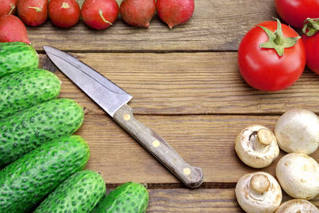 Fresh Vegetables And Knife On The Kitchen Rustic Rough Wooden Tabletop. Tomatoes, Cucumbers, Mushrooms, Radish photo
