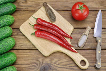 top seven: Three Hot Chili Peppers on Wood Cutting Board, One Tomato, Fresh Seven Cucumbers, Salt And Pepper In  The Small Wood Spoon, Kitchen Knife On The Rough Rustic Wooden Tabletop