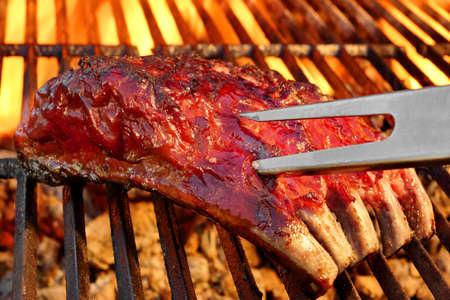barbecue: Barbacoa a la parrilla sabroso picante ahumado Costillas de cerdo marinadas A Summer Party. Caliente Parrilla de carb�n Con Flaming Embers En El Fondo