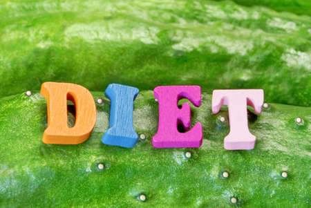home grown: Wooden Sign DIET On Fresh Home Grown Cucumbers Close-up Green Background