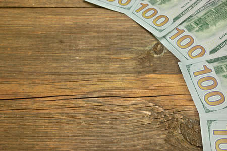 bribes: Five New One Hudred Dollar Bill On The Rough Wood Background