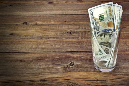 Glass  With Money  for Big Tip Or Savings With Dollar Bills On Rough Wood Background photo