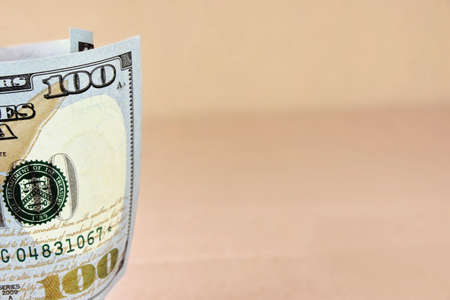 one hundred dollar bill: Rolled New American One Hundred Dollar Bill On The Beige Floor Background Stock Photo