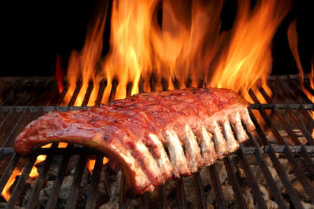 grill: BBQ Baby Back Spicy Marinated And Smoked Pork Ribs On The Hot Charcoal Grill With Bright Flames On Black Background. Good Snack For Outdoor Party Or Picnic Stock Photo
