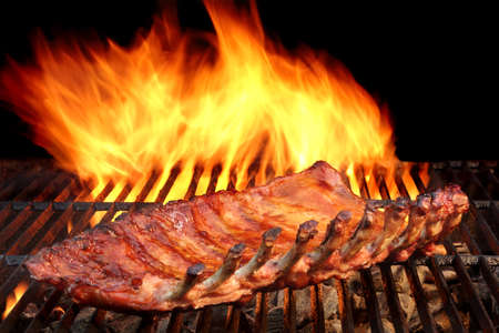 BBQ Baby Back Spicy gemarineerd en gerookt varkensvlees ribben op de Hot Charcoal Grill Met Heldere vlammen op zwarte achtergrond. Goede snack voor Outdoor Party of picknick Stockfoto