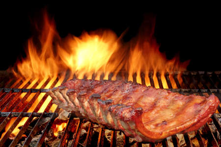 smoked: BBQ Baby Back Spicy Marinated And Smoked Pork Ribs On The Hot Charcoal Grill With Bright Flames On Black Background. Good Snack For Outdoor Party Or Picnic Stock Photo
