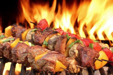 barbecue: Kababs Barbacoa de carne en el Hot Grill Primer plano. Llamas de fuego en el fondo