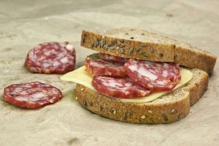 dry sausage: Single Sandwich With Dried Smoked Sausages Slices And Cheese On The Paper Bag Background Close-up Stock Photo