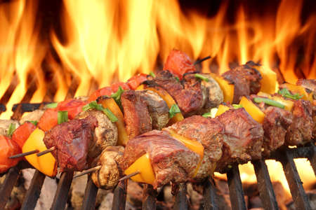 skewer: Barbecue Beef Kababs On The Hot Grill Close-up. Flames of Fire In The Background Stock Photo