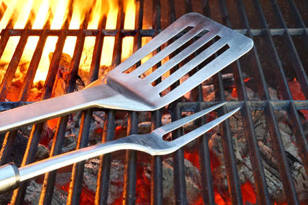 Empty Hot Flaming Charcoal Grill With BBQ Tools. Summer Outdoor Party Or Picnic Concept